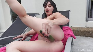 Solo girl inserts large cucumber up her pink holes