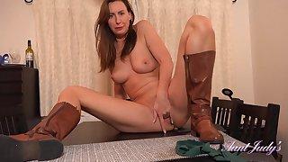 British dominatrix Lara Latex masturbating on table top in sexy leather boots
